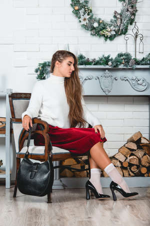 gorgeous young female in a red skirt and white pullover sitting in retro armchair on a christmas decorated wall background. Erotic legs in white socks and black varnish high heells