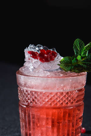 Cold cocktail with ice and garnet seeds, piece of pomegranate behind on dark background