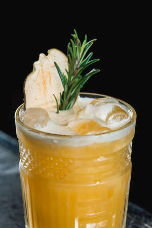Cold Whiskey Sour Cocktail with ice and apple chips, piece of thyme on top Foto de archivo