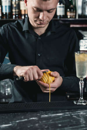 bartender making cocktail. slicing a long ribbon of lemon peel