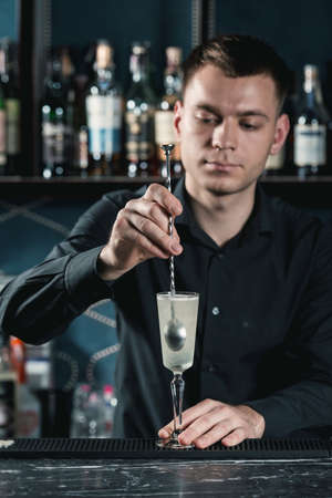 bartender making French 75 Cocktail. Mixing ingredients in a glass. Bar on a background