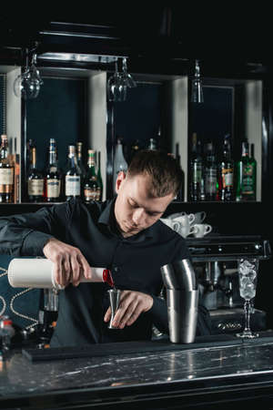 bartender making French 75 Cocktail pouring fluid into glass. Bar on a background