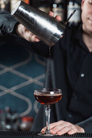 bartender making Boulevardier Cocktail pouring fluid into glass. Bar on a background