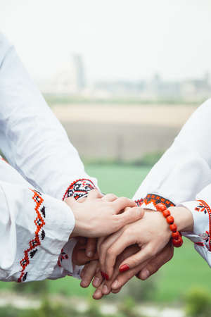 people are dressed in traditional Ukrainian clothes holding their hands together, success unification of the nation concept 스톡 콘텐츠