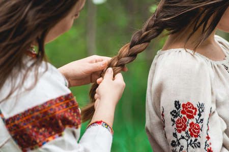 Girlish leisure concept. Sisters, best friends in traditional ukrainian clothes making braid, hairdo each other