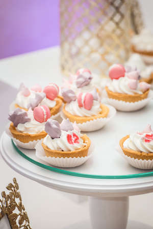 white stand with cupcakes on a candy bar table Stock Photo