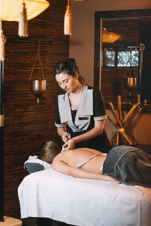 Young charming girl on a panchakarma procedure laying on a massage table. beautiful woman spending time at modern spa cabinet relaxing. Soft yellow light.