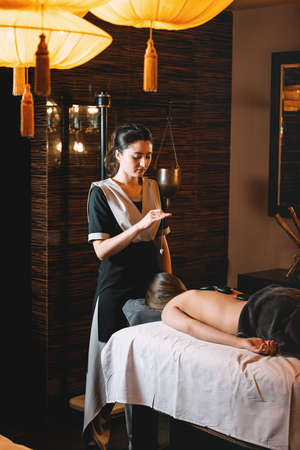 Specialist making biolocation with crystal pendulum. Young charming girl on a panchakarma procedure laying on a massage table. beautiful woman spending time at modern spa cabinet relaxing. Soft yellow light.