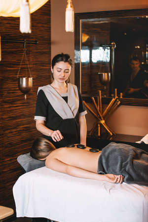 Specialist making biolocation with crystal pendulum. Young charming girl on a panchakarma procedure laying on a massage table. beautiful woman spending time at modern spa cabinet relaxing. Soft yellow light. Stock Photo