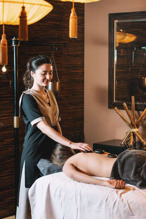 Specialist making hot stone massage to a client. Young charming girl on a panchakarma procedure laying on a massage table. beautiful woman spending time at modern spa cabinet relaxing. Soft yellow light. Stock Photo