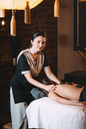 Specialist making hot stone massage to a client. Young charming girl on a panchakarma procedure laying on a massage table. beautiful woman spending time at modern spa cabinet relaxing. Soft yellow light.