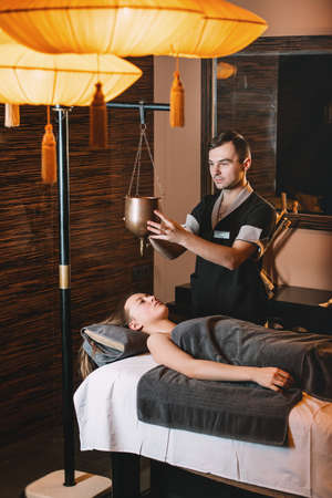 Specialist making shirodhara massage form of ayurveda therapy. Young charming girl on a panchakarma procedure laying on a massage table. beautiful woman spending time at modern spa cabinet relaxing. Soft yellow light. Stock Photo