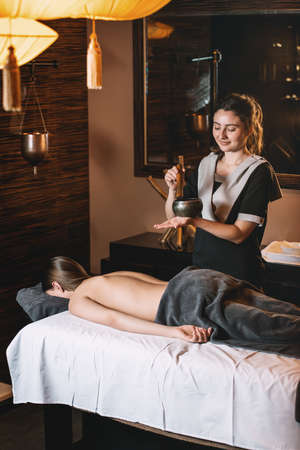 Specialist holding in hands Brass Hammer Singing Bowl. Young charming girl on a panchakarma procedure laying on a massage table. beautiful woman spending time at modern spa cabinet relaxing. Soft yellow light.