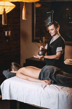 Specialist holding in hands Brass Hammer Singing Bowl. Young charming girl on a panchakarma procedure laying on a massage table. beautiful woman spending time at modern spa cabinet relaxing. Soft yellow light. Stock Photo