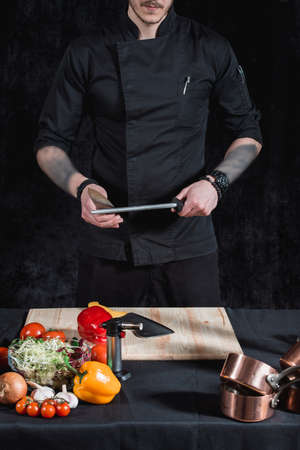 Young attractive man chef in black uniform hands in tattoos holds two knives. black background. no face