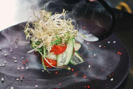 fresh organik salad on a round stone plate processed with smoke