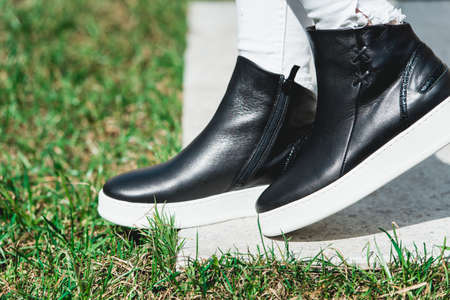 Side View Of Womans Black Leather Ankle Boots. Outdoor Shot Over White Stone in park. white sole