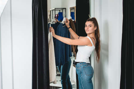 Smiling young beautiful woman shopping, i a fitting room in fashion mall, making decision on what to buy, holding two hangers with different sweaters, trying to choose between new clothes. Girl wearing blue jeanse and white T-shirt