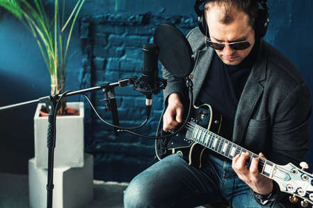 Close up of a man singer in a headphones with a guitar recording a track in a home studio. Man wearing sunglasses, jeans, black shirt and a jacket. side view