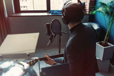 Close up of a man singer in a headphones with a guitar recording a track in a home studio. Man wearing sunglasses, jeans, black shirt and a jacket. Look from back, window on a bakground Stok Fotoğraf
