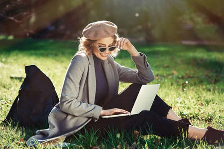 Work outdoors benefits. Education technology and internet concept. Smiling girl with stylish sunglasses and beret work with laptop in park sitting on grass. Natural environment office.