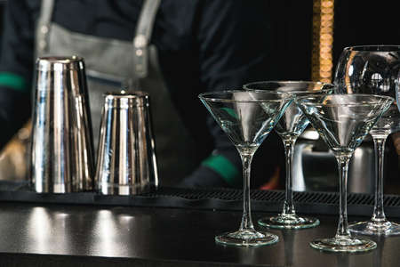 Vasos para una margarita, martini, grog y licor en un bar en el restaurante, contra el fondo de la pared del bar bar. Foto de archivo