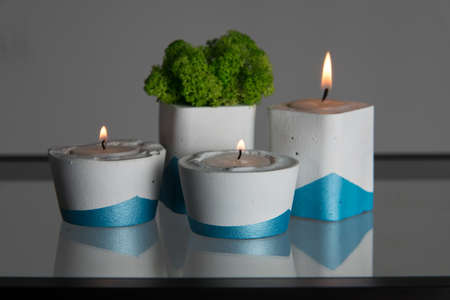 candles and moss in white and blue concrete candle holders. Stock Photo