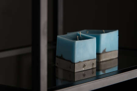 blue candle on a gray concrete base. Stock Photo