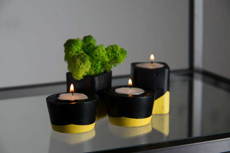 candles and moss in black and yellow concrete candle holders. Stock Photo