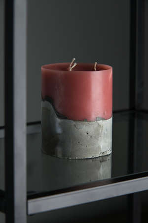 red candle on a gray concrete base.