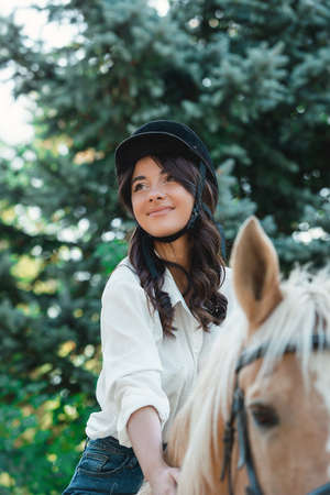 Portrait of young brunette woman in a white shirt and helmet on a horse. learns to ride a horse. riding lessons in a park
