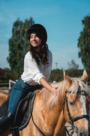 Portrait of young brunette woman in a white shirt and helmet on a horse. learns to ride a horse. riding lessons on a horse epodrom Standard-Bild