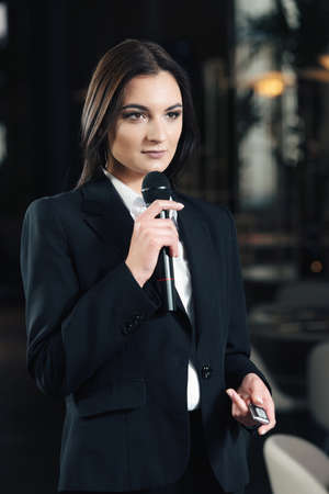 Business and speech topic: woman in a white shirt holding a black microphone, indoor