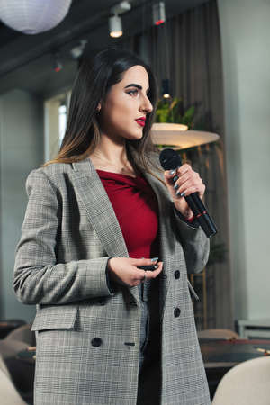 Business and speech topic: woman in a red shirt and gray jacket holding a black microphone in one hand and a clicker in another, indoor