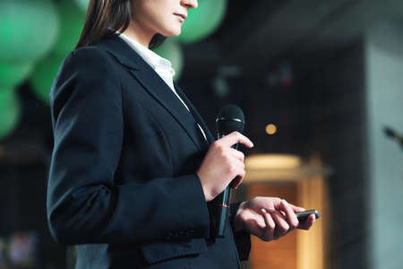 Business and speech topic: woman in a white shirt and black jacket holding a black microphone in one hand and a clicker in another, indoor