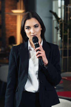 Business and speech topic: woman in a white shirt and black jacket holding a black microphone in a hand , indoor Stock Photo