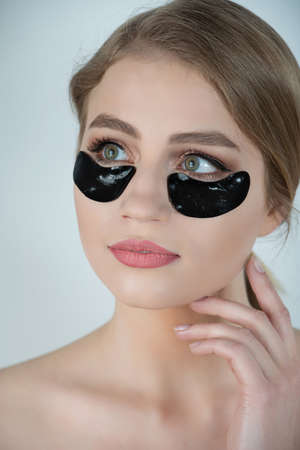 Under Eye Skin Black Patch. Closeup Of Beautiful Young Woman Face With Moisturizing Collagen Mask Pad On Healthy Fresh Facial Skin On White Background. High Resolution. Standard-Bild