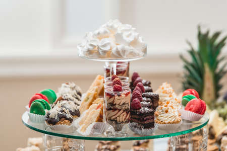 glass stand with cupcakes and other sweets on a wedding candy bar table. Foto de archivo