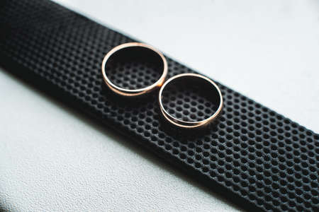 Close up of wedding rings on a black leather belt