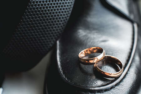 Close up of wedding rings on a black leather shoe.