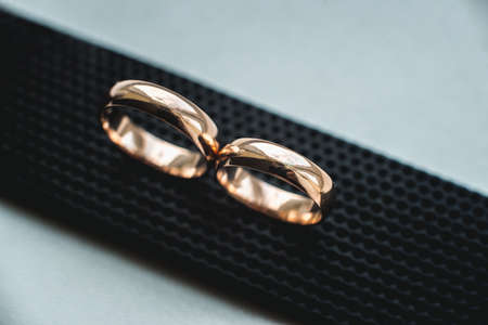 Close up of wedding rings on a black leather belt.