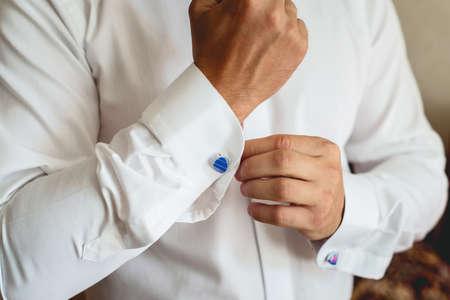 Un hombre abrocha un gemelo azul en la camisa. Cerca de la mano de un hombre vestido con una camisa blanca y gemelos. Foto de archivo