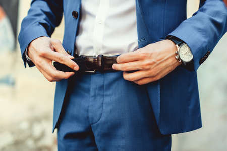 Groom in blue pants and a white shirt fastens his leather belt. grooms mourning. Wedding details. Concept and composition.