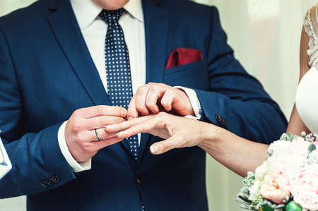 exchanging wedding rings. Groom puts a ring on the bride's finger. groom in a blue suit. The bride's bouquet