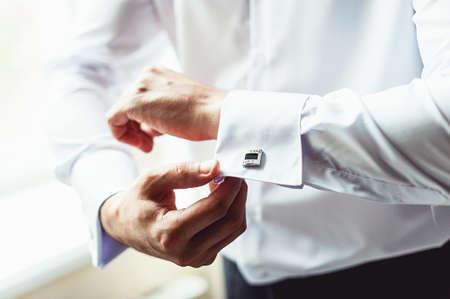 A man fastens black cufflink on the shirt. Close up of a man hand wearing a white shirt and cufflinks.
