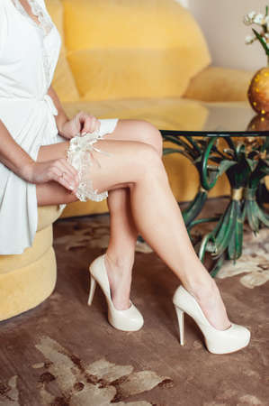 Bare feet of a bride sitting her high hill shoes and bathrobe during wedding preparations