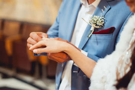 exchanging wedding rings. Groom puts a ring on the bride's finger. groom in a blue suit. Church