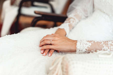 Close up of a brides hand on her lap. Wedding ring