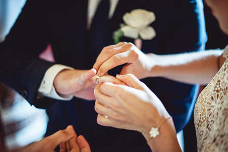 exchanging wedding rings. Bride puts a ring on the groom's finger. groom in a black suit. The bride's bouquet