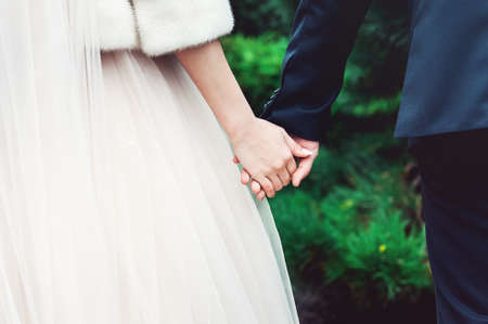Bride and groom holding hands on a green background. Wedding day Imagens